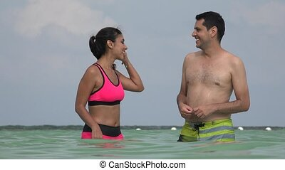 Young Couple Wearing Bathing Suits Having Fun In Ocean