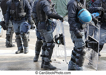 policemen in riot gear with hardhat while patrolling the...
