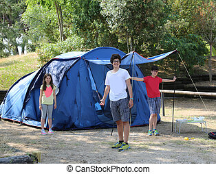 Three smiling children mount the tent in the campsite