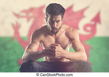 Muscular man with Welsh Flag behind