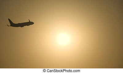 Silhouette of passenger airplane flies across sun at sunset....