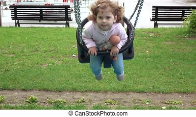 Girl riding on a swing - Curly-haired girl riding a wooden...