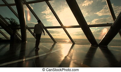 Silhouette of business man walking and stand near window in modern office building
