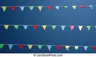 Small triangular waving flags on blue sky
