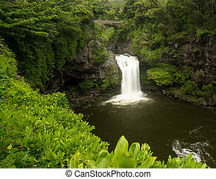 Waterfall under road bridge at Seven Sacred Pools Maui -...