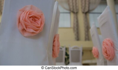 Interior of a wedding hall decoration ready for guests.Beautiful room for ceremonies and weddings. Nice decor with pink roses on white chairs