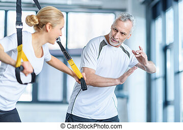 sportswoman and senior trainer training with resistance band...