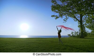 Young beautiful Woman in red dress with red transparent cloth is walking on the sea at sunrise.