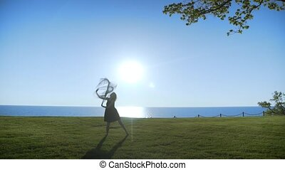 Young beautiful Woman in black dress with black transparent cloth is dancing on the sea at sunrise.