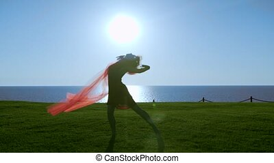 Young beautiful Woman in red dress with red transparent cloth is dancing on the sea at sunrise.