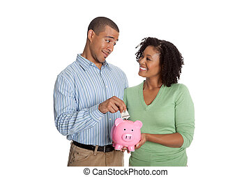Man putting money into piggy bank held by woman, smiling...