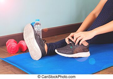 Tying sport shoes, Asian woman getting ready for weight...