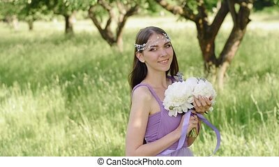 Portrait of a beautiful girl with professional make-up. Caucasian brunette woman posing and looking at camera in lilac or purple dress in green garden near apple fruit tree.