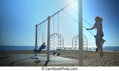Young beautiful brunette woman is riding on a swing.