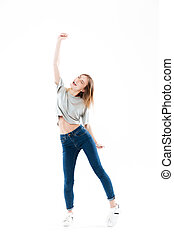 Full length portrait of a cheerful happy girl celebrating...