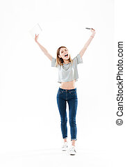 Full length portrait of a happy cheerful girl holding...
