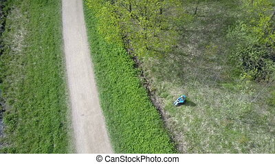 Aero view from the drone on the young woman the reading book...