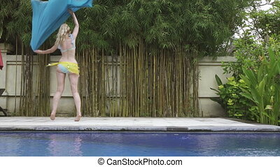 young slender woman dances an oriental dance near pool in...