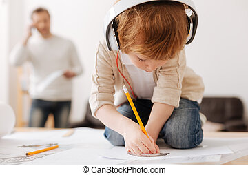 Attentive boy bowing head while drawing picture - Do it in...