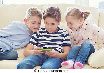 Three little children playing with tablet pc
