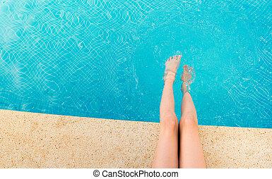 Young woman splashing feet in pool