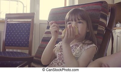 A girl eating sandwich - A girl sitting in the chair and...