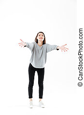 Full length portrait of a woman standing with outstretched...