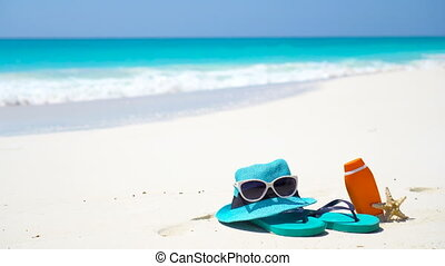 Beach accessories - straw hat, flip flops, bottle of cream...