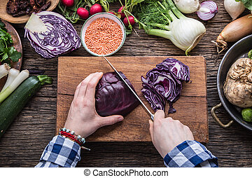 Hand cutting vegetables.Women hands is slicing cabbage on wooden board near vegetables