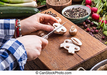 Hand cutting vegetables.Women hands is slicing mushrooms on wooden board near vegetables
