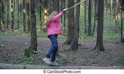 Little girl is walking on log - Little girl is walking on...