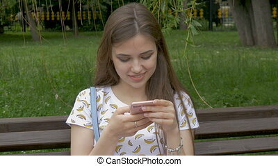 A beautiful white girl is reading sms on a smartphone. I got...
