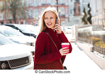 Smiling young caucasian woman walking outdoors talking by...