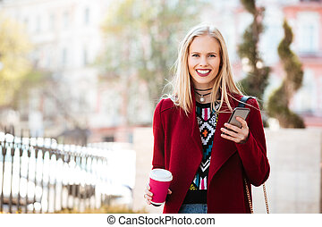 Smiling young caucasian woman walking outdoors chatting -...