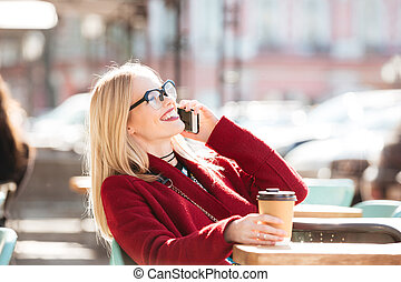 Happy young caucasian lady talking by phone drinking coffee....