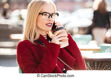 Amazing young caucasian woman talking by phone drinking...