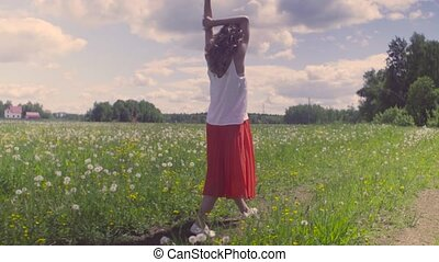 Young woman walking on the meadow - Rear view of young woman...