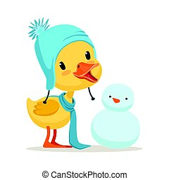 Little yellow duck chick wearing blue knitted hat playing...