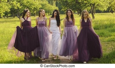 Beautiful bride and bridemaids in purple dresses walking in...