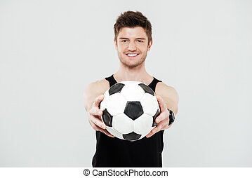 Cheerful young sportsman with foot ball