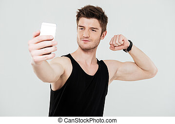 Handsome young sportsman with phone make selfie
