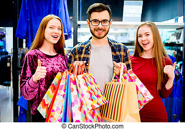 Friends shopping in mall - A group of friends is shopping in...
