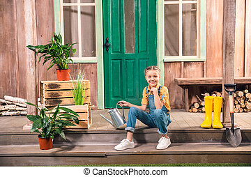 Adorable smiling little girl sitting on porch with watering can