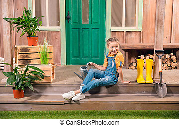 Adorable smiling little girl sitting on porch with watering can and looking away