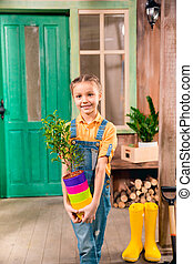 Adorable little girl holding colorful flower pots with home plant and smiling at camera