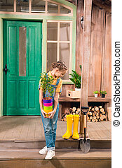 Adorable little girl holding colorful flower pots with home plant and looking down