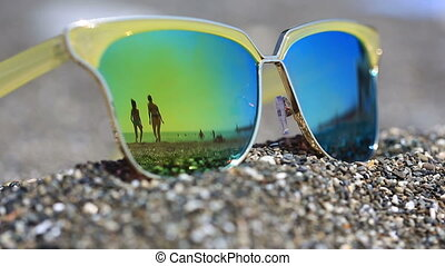 Sunglasses on the sand, the beach with the resting people is...