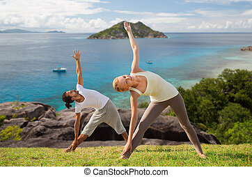 happy couple doing yoga outdoors - fitness, sport and people...