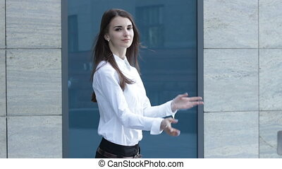 cute business girl with crossed hands smiling in the street