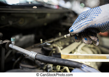 mechanic with dipstick checking motor oil level - car...